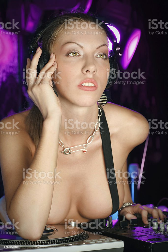 Sexy blonde thoughtful lady DJ in suspenders at night club royalty-free stock photo