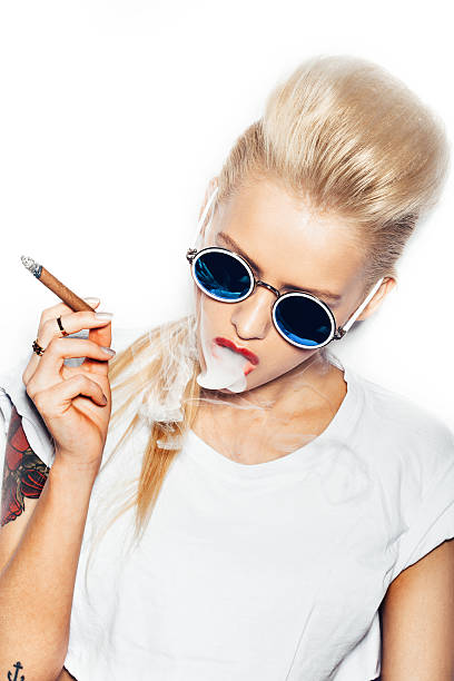 Sexy blonde woman in sunglasses smoking cigar stock photo