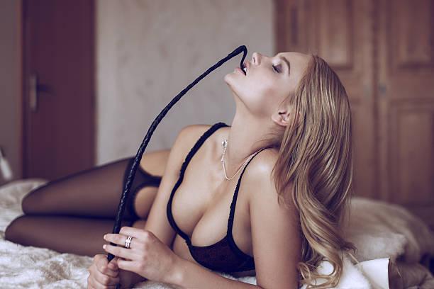 Sexy blonde woman in underwear bite whip stock photo