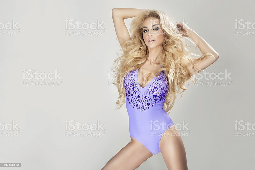 Sexy blonde woman with long curly hair posing in swimsuit. royalty-free stock photo