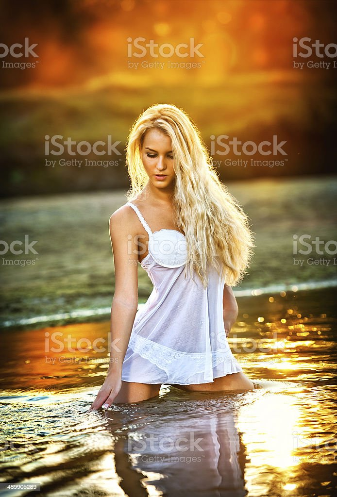 Sexy blonde woman with wet lingerie in river during sunset stock photo