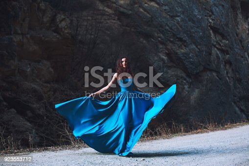 Sexy brunette at the foot of the mountain in a blue dress