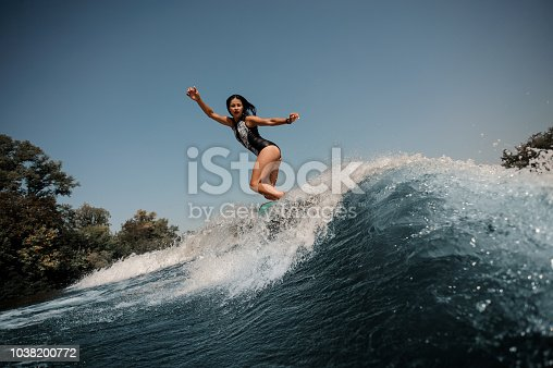 Sexy brunette girl in the black and white swimsuit jumping on the wakeboard on the background of a lakeside and sky