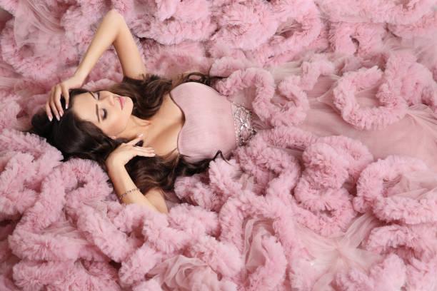 sexy brünette in rosa kleid. schönheit welliges haar. schöne frau liegen in wunderschönen langen kleid. - tüllkleid stock-fotos und bilder
