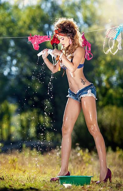 Sexy brunette putting nasse Kleidung in der Sonne trocknen – Foto