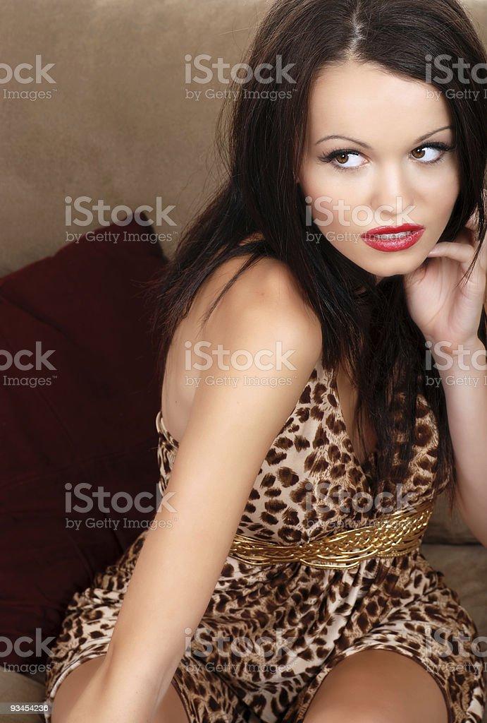 sexy brunette sitzend auf einem beige Sofa Lizenzfreies stock-foto