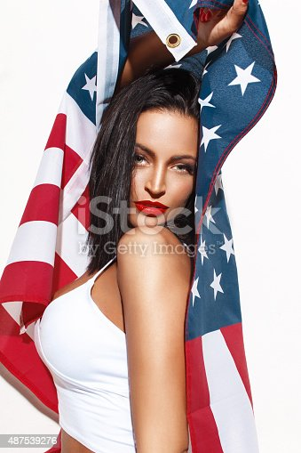 istock Sexy brunette woman holding USA flag 487539276