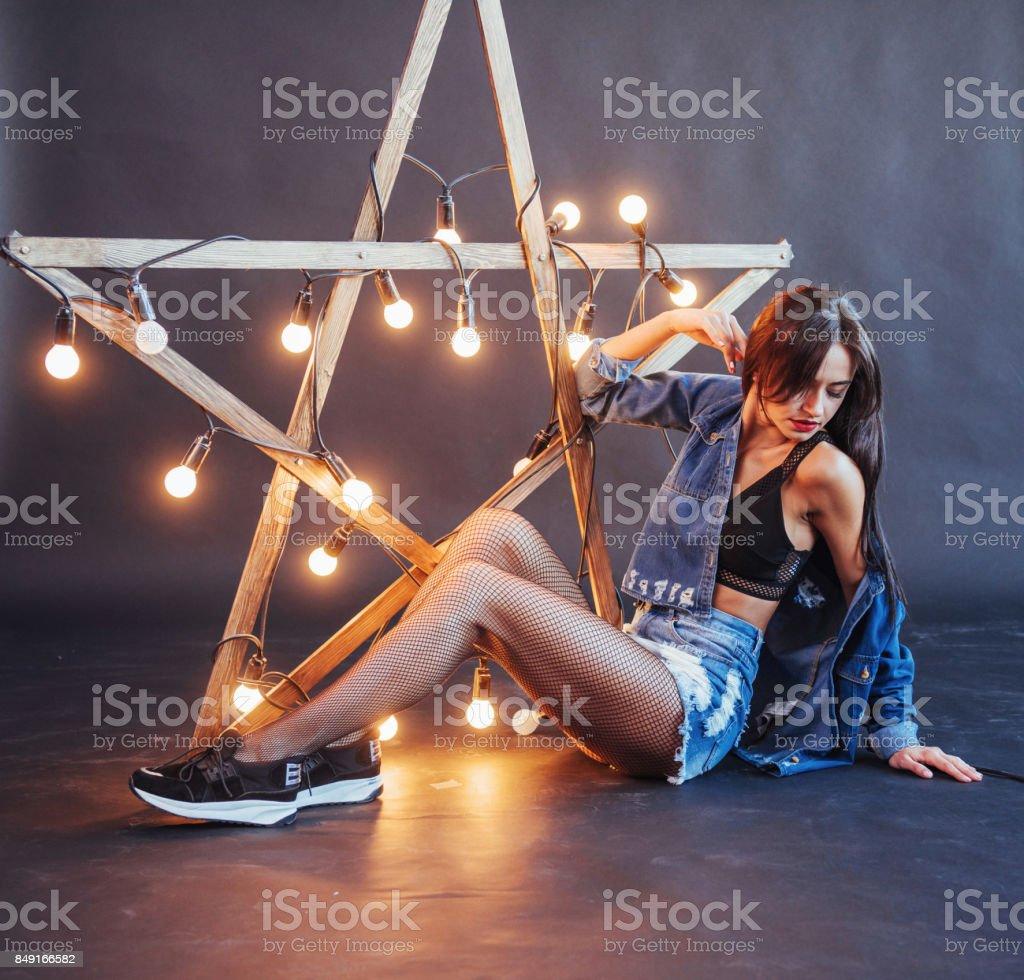 Mulher morena sexy em jeans legal no estúdio. Estrela de madeira com luzes em um fundo preto - foto de acervo
