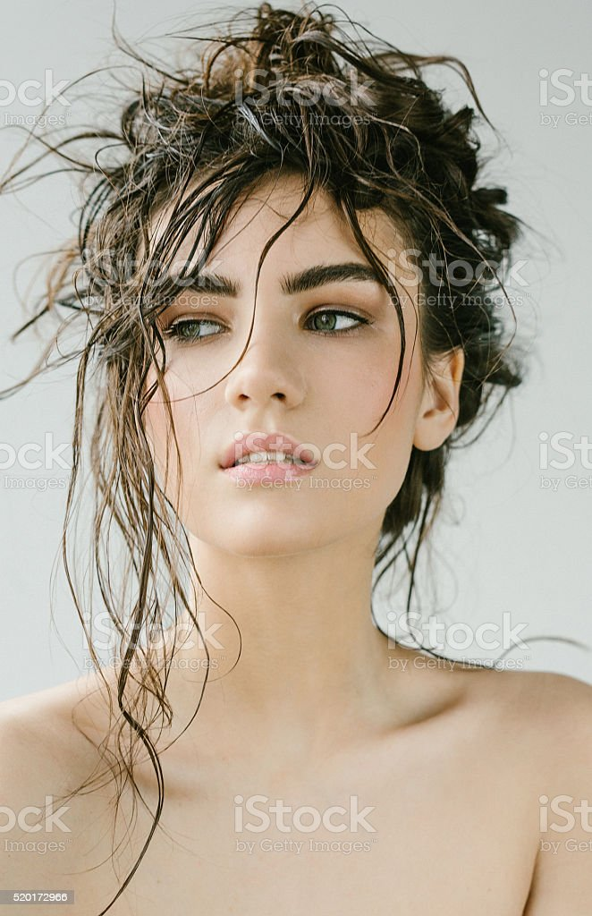 Sexy brunette woman with wet hair beauty on grey stock photo