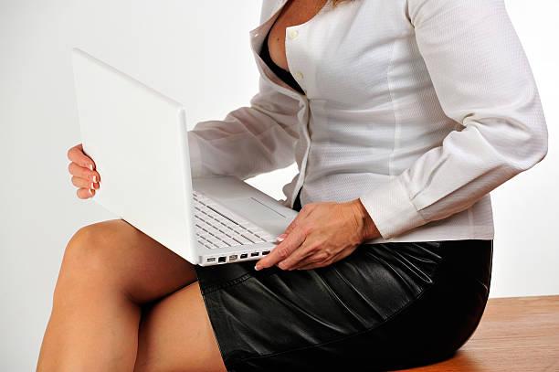 Sexy Mulher de negócios sentado na mesa segurando um laptop. - foto de acervo