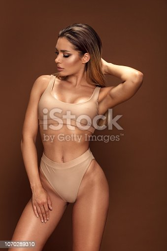 Sexy tanned woman in fashionable swimsuit posing against studio background.
