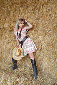 istock Sexy country cowgirl posing on hay background 530298137