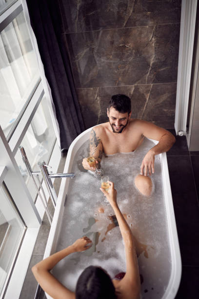 Sexy couple enjoying and relaxing in the bathtub and drinking champagne top view stock photo