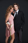 An attractive young couple flirts with each other in attractive evening wear. They are clearly attracted to one another like lovers with a great deal of passion.