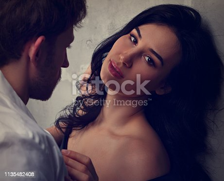 956369394 istock photo Sexy couple portrait. Man in white shirt hugging his sensual beautiful girlfriend with much emotion. Closeup 1135482408