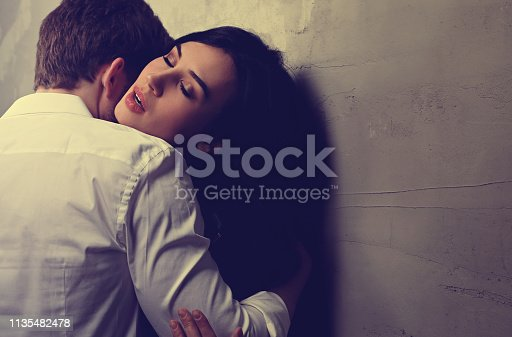 956369394 istock photo Sexy couple portrait. Man in white shirt kissing his sensual beautiful girlfriend in neck with much emotion. Toned color 1135482478