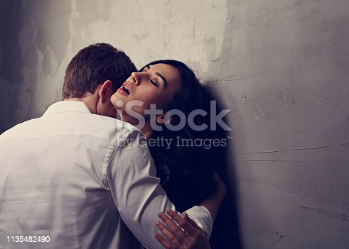 956369394 istock photo Sexy couple portrait. Man in white shirt kissing his sensual beautiful girlfriend in neck. Happy Valentines day 1135482490