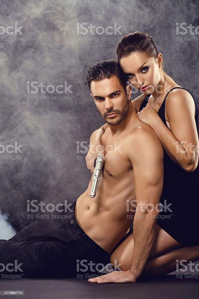 sexy couple posing with gun stock photo & more pictures of 2015 | istock
