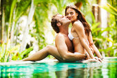 Boyfriend and a girlfriend kissing in the pool surrounded by tropical nature.