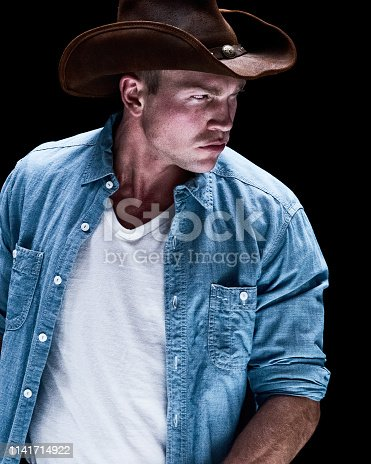 Very sexy cowboy standing in black space
