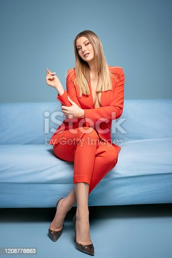 Sexy modern young woman in fashionable elegant clothes sitting on sofa, relaxing.
