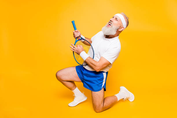 Sexy emotional cool pensioner grandpa practising rock music on a  sport equipment, stands on one knee, yell and shout. Body care, hobby, weight loss, lifestyle, strength and power, health stock photo