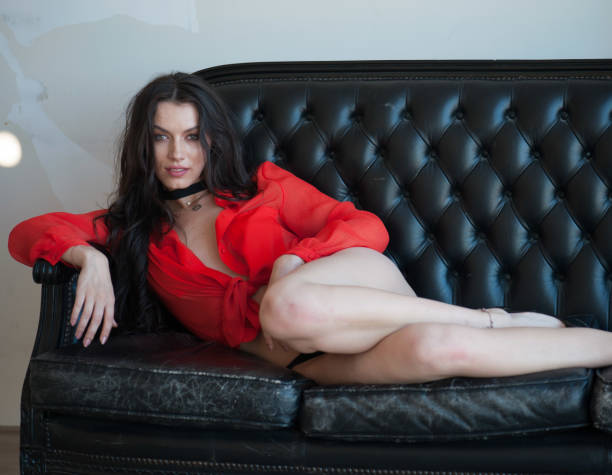 Sexy modelo sentado en el sofá - foto de stock