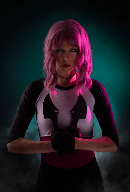 Sexy female assassin with pink hair wearing black holding weapons stock photo