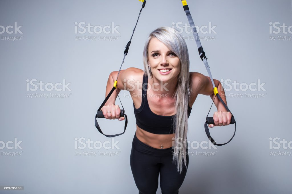 Sexy female fitness model training on a home training device in a...