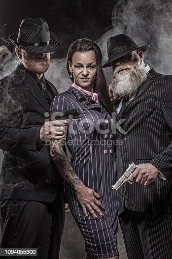 Sexy senior brunette female gangster boss with bodyguards