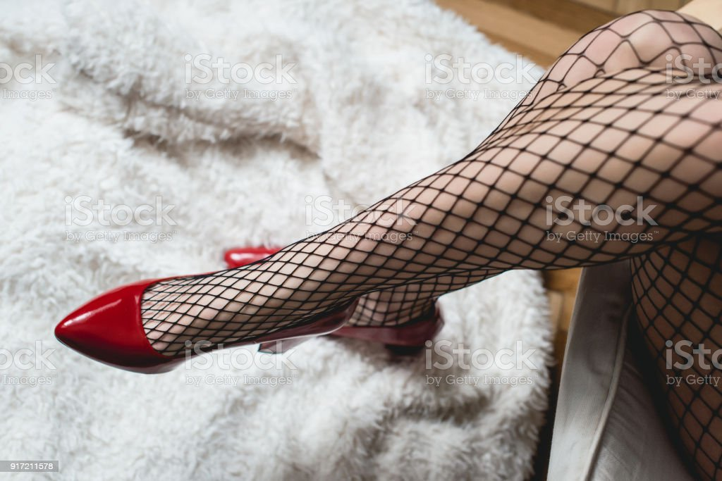 a6017b07a7b Sexy female legs in high heel red shoes and fishnet stockings. Retro style  - Stock image .