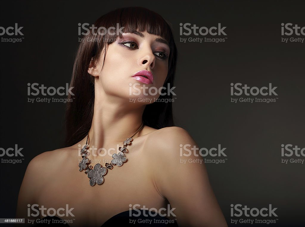 Sexy female model in fashion necklace on dark background stock photo