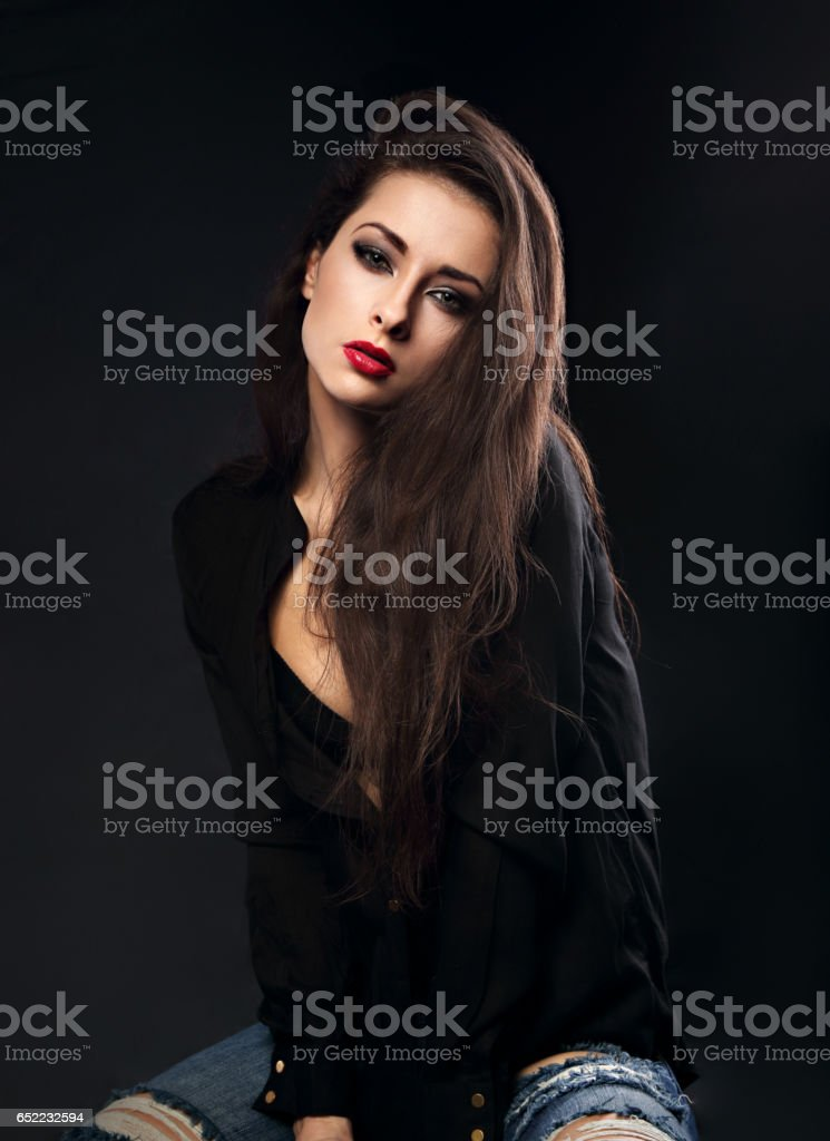 Sexy female model with long brown hair posing in black shirt and ripped jeans on dark background with red lipstick stock photo