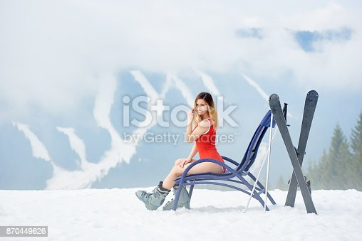 istock Sexy female skier on blue deck chair near skis at ski resort 870449626