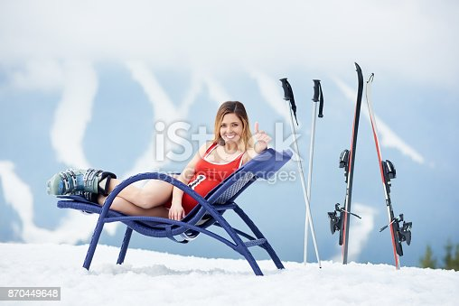 istock Sexy female skier on blue deck chair near skis at ski resort 870449648