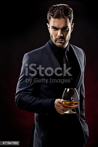 471947536 istock photo sexy gentleman holding glass of whiskey 471947552