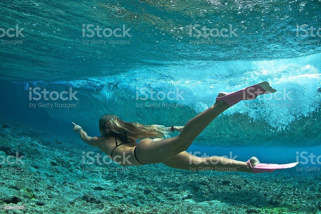 Sexy girl bodysurfs a wave stock photo