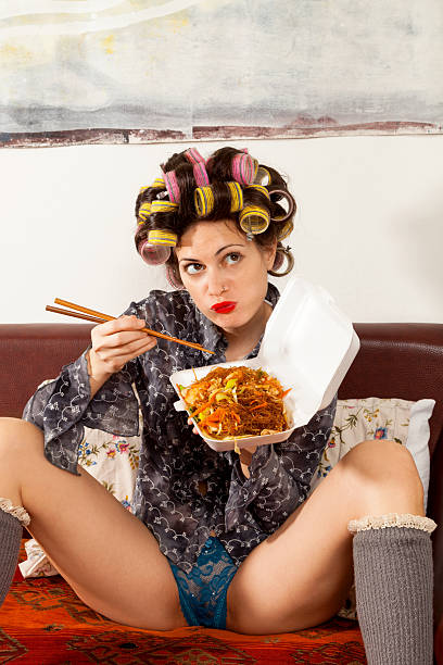 sexy girl eating spaghetti on the couch stock photo