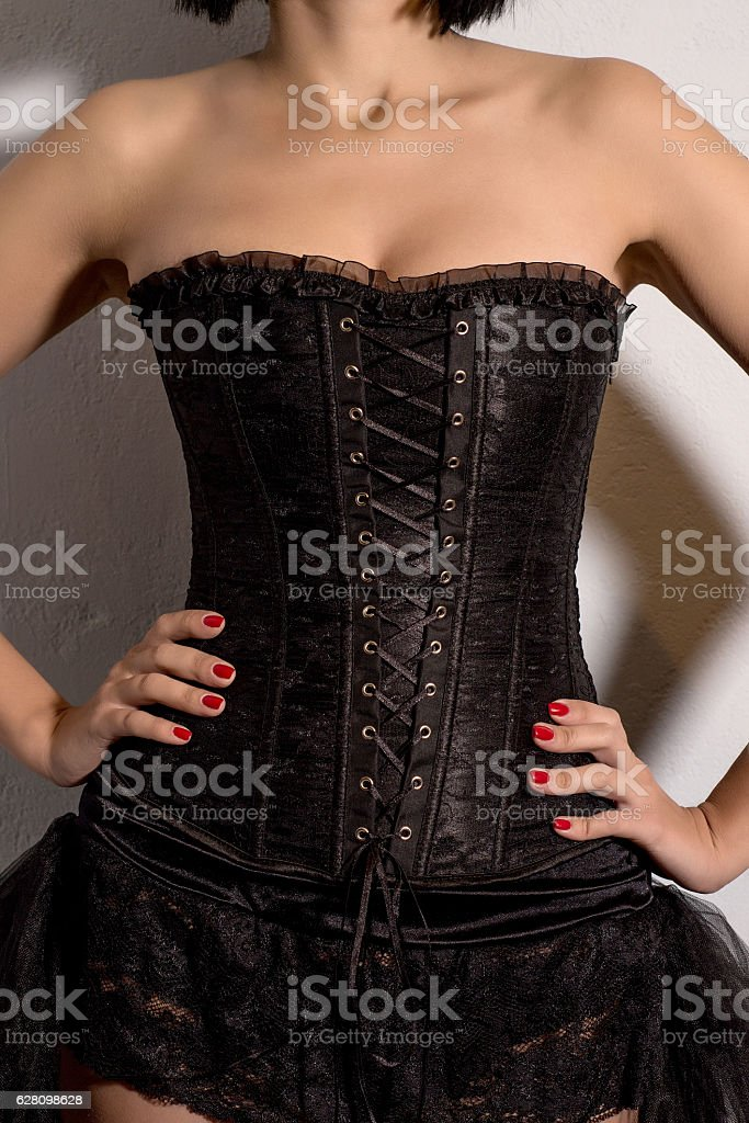 Sexy girl in a black corset standing near blue wall stock photo
