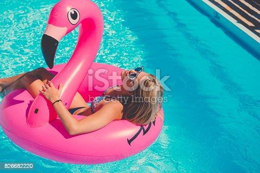 istock Sexy girl in bikini wearing sunglasses on inflatable flamingo 826682220