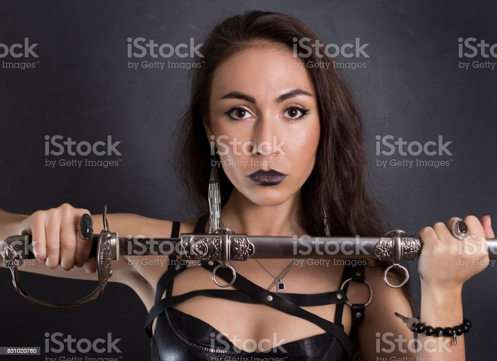 f0d96677b Sexy girl in black lingerie and sword belt on gray background. Gets a sword  from a sheath. - Stock image .