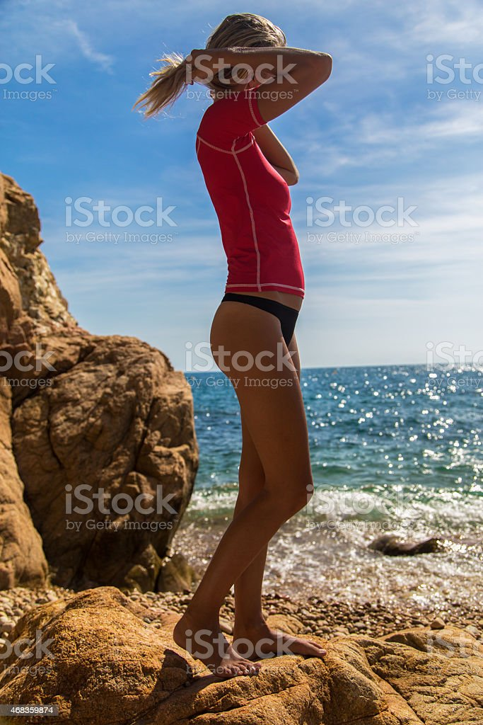 Sexy girl in sportwear and tanga on the rocky beach royalty-free stock photo