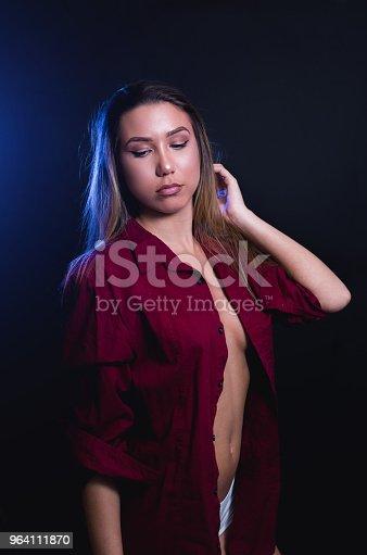 A sexy caucasian brunette girl in a dark studio shoot wearing a velvet shirt and white underwear