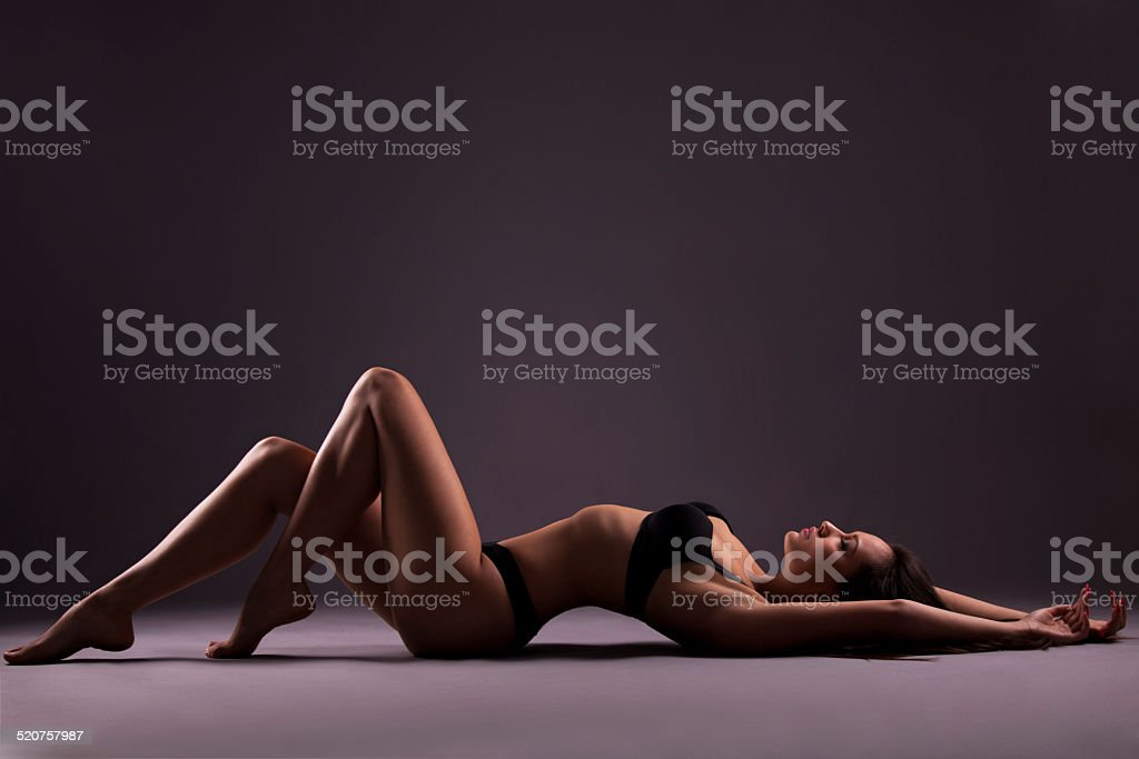 Sexy girl lying on the floor in black lingerie stock photo