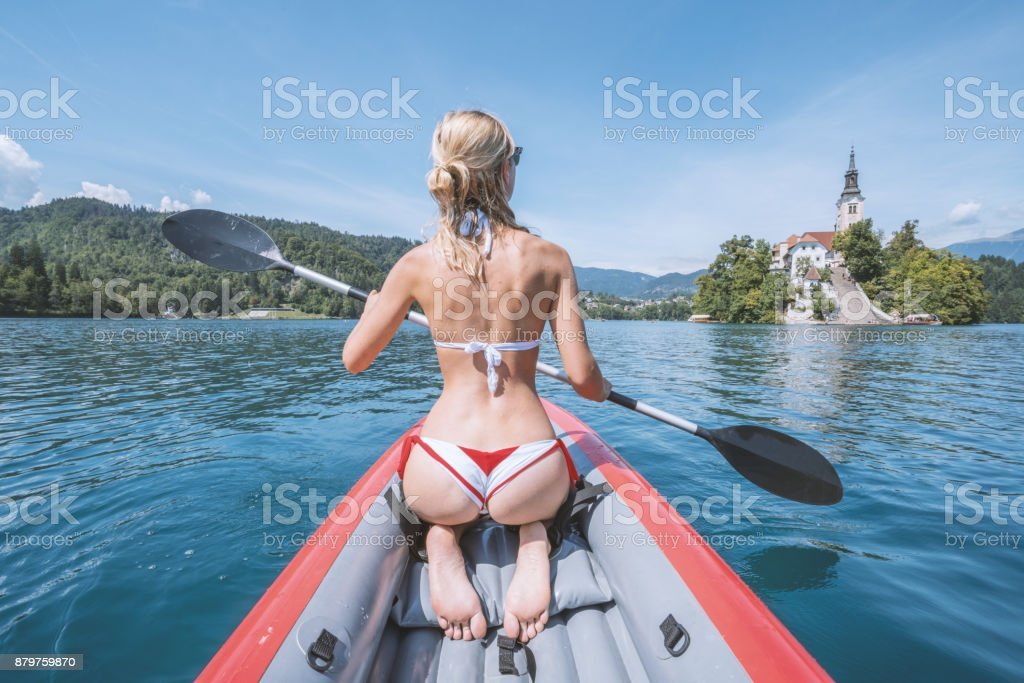Sexy girl paddling red canoe in Slovenia stock photo