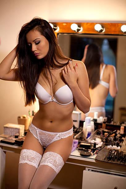 sexy mädchen in weißen dessous posieren von der spiegel - schmaler tisch stock-fotos und bilder