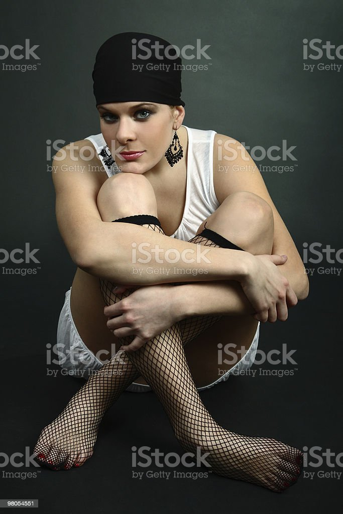 Sexy girl sitting on floor wearing fence net stockings royalty-free stock photo