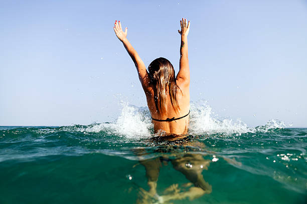 sexy girl swim sea waves hands up splash back view stock photo