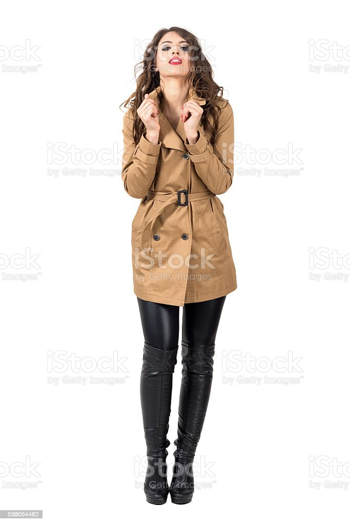 Sexy glamorous woman holding beige coat collar looking at camera stock photo