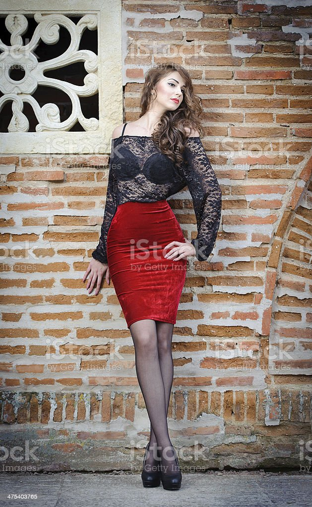 Sexy gorgeous young woman near old wall stock photo